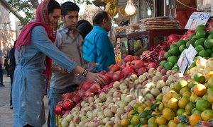 Yasmin Khan choosing pomegranates, the nation's favourite fruit, at an Iranian market.