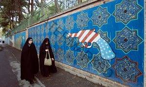 Iranian women walk past a mural outside the former US embassy in Tehran.
